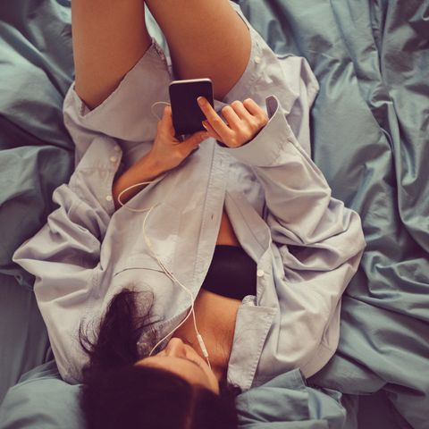 Girl in bed using smartphone