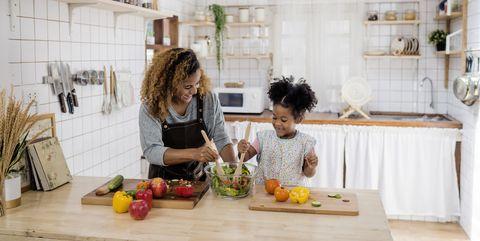 meisje leert koken van haar moeder