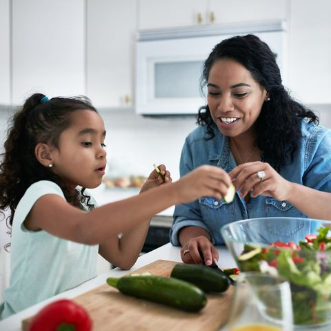 girl learning to prepare meal from mother