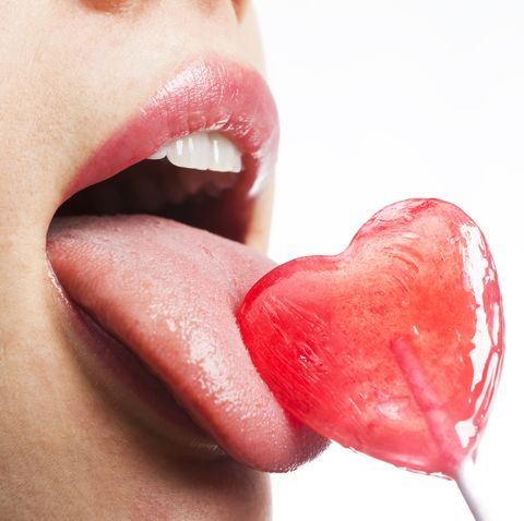Girl licks heart lollipop