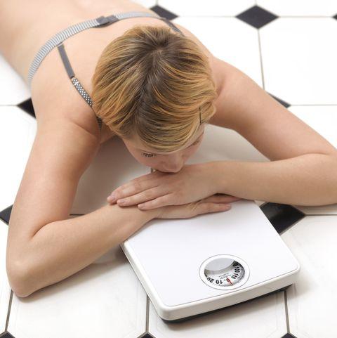 Girl obsessed with dieting on bathroom floor