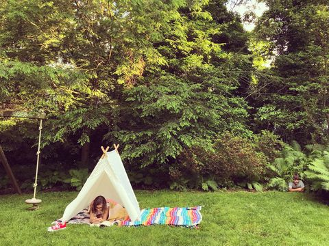 girl reading in a tent in the garden while little brother peeks out of ferns