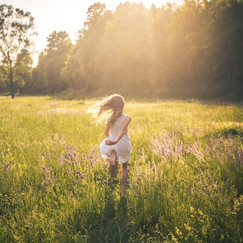 Girl running outside through grass