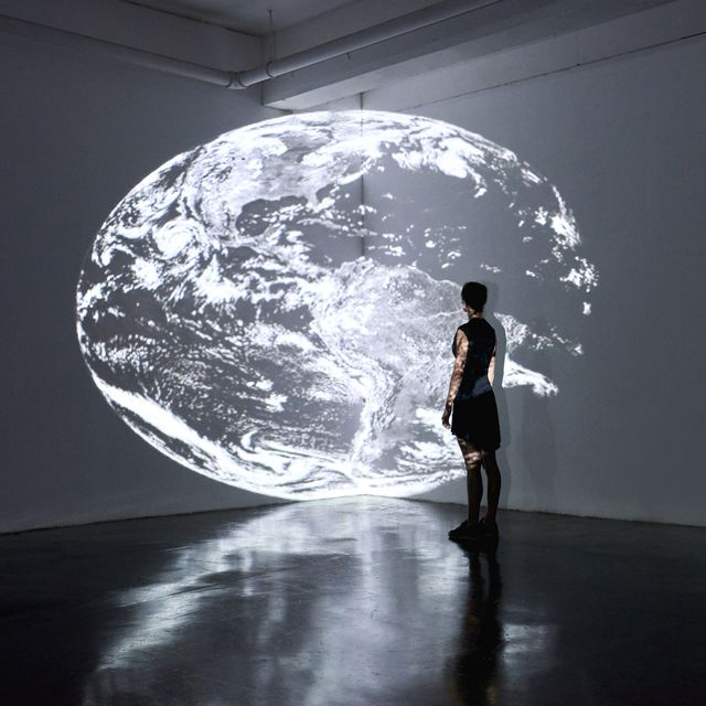 girl standing in gallery space looking at large scale projection of planet earth