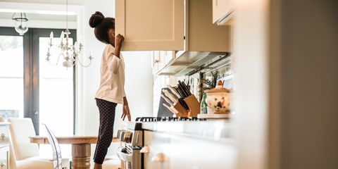 girl standing on tippy toes looking in cupboard