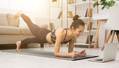 girl training at home, doing plank and watching videos on laptop