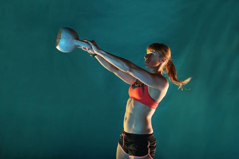 Girl training with kettlebell, green background