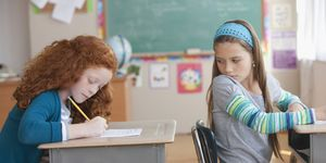 Girl trying to copy off of student's paper in classroom