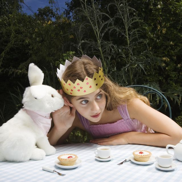 girl 10 11 wearing crown having tea party with toy rabbit