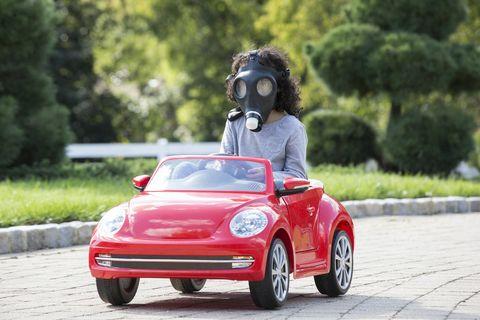 Meisje met gasmasker in speelgoedauto