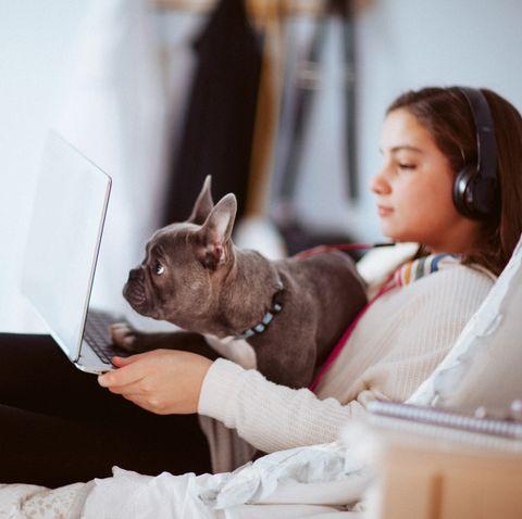 girl with headphones using computer in her bedroom
