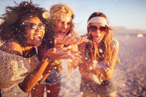 Girls blowing confetti from their hands on a beach