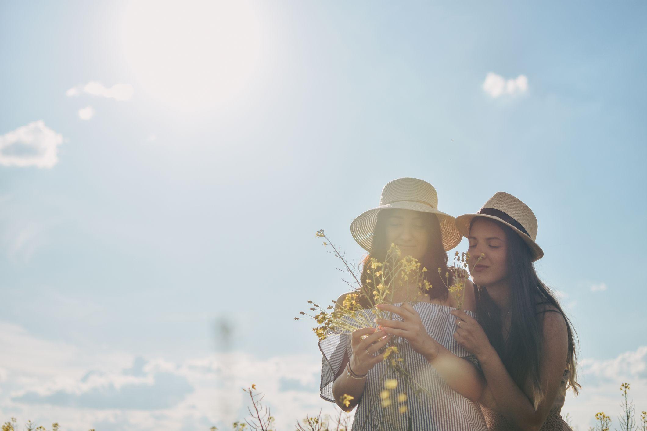 to jenter som holder hverandre og gule blomster