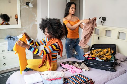Girls packing clothes in suitcase for travel