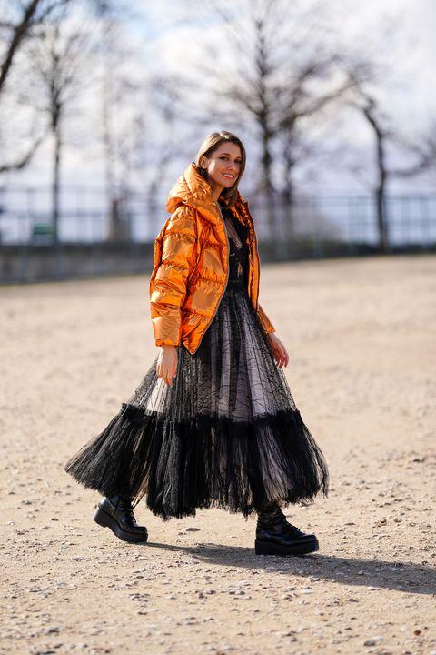 paris, france   february 25 landiana cerciu wears an orange shiny puffer coat, a black lace mesh dress, black boots, outside dior, during paris fashion week   womenswear fallwinter 20202021, on february 25, 2020 in paris, france photo by edward berthelotgetty images
