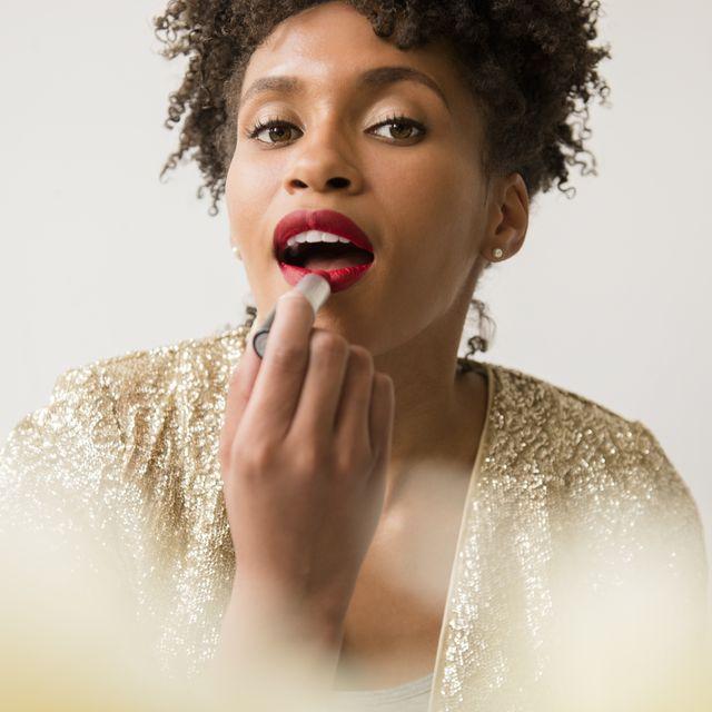 glamorous black woman applying red lipstick