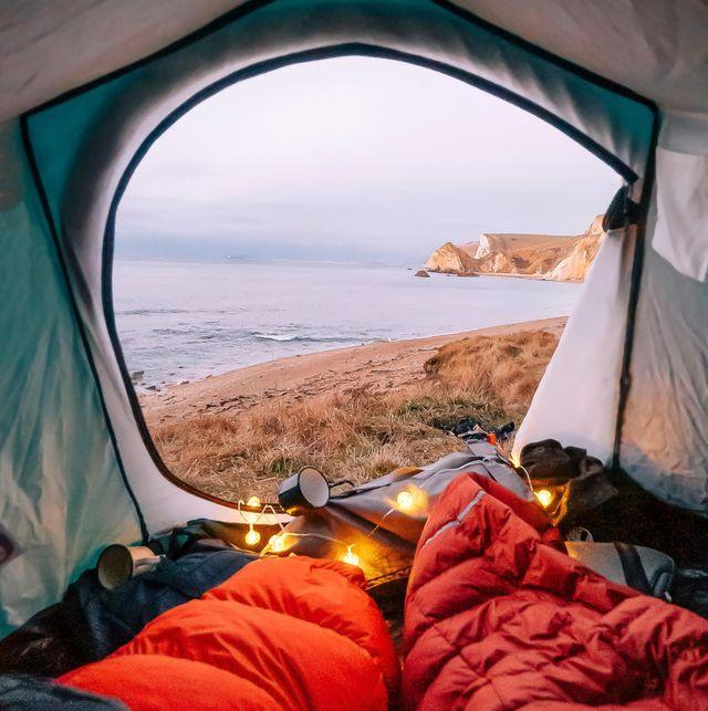 tienda de campaña frente a la playa con sacos de dormir rojos tazas y el amanecer de fondo