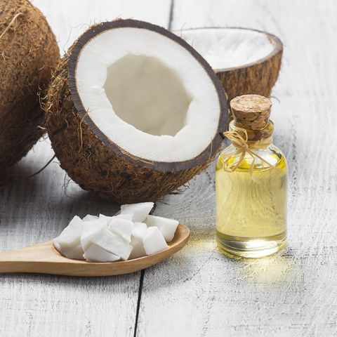 glass bottle of coconut oil with fresh coconut fruit on rustic background, alternative theraphy medicine concept, cocos nucifera