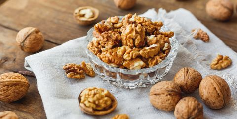 Glass bowl with walnuts on rustic homespun napkin. Healthy snack.