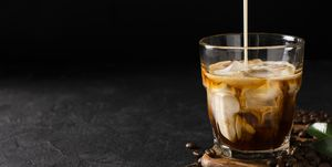glass cold brew coffee with ice and milk on black or dark background