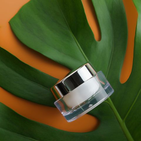Glass Jar Of Moisturizer On Green Leaf Over Orange Background