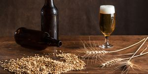 Glass of beer on the table, with wheat malt, barley and bottles