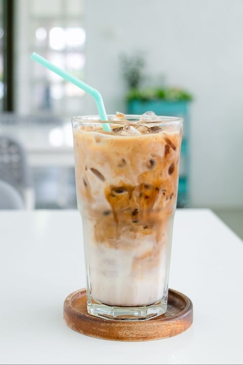 a glass of ice coffee on the white table in coffee shop