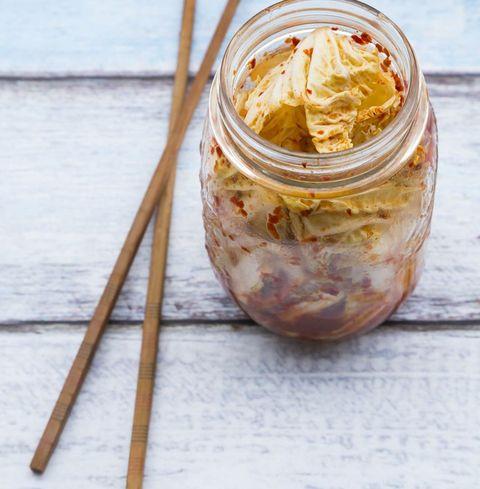 Verre de Kimchi et baguettes sur bois