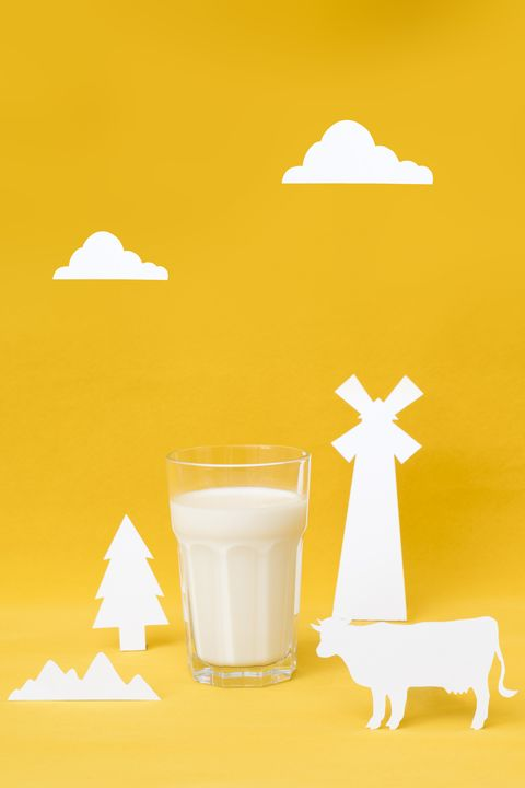 glass of milk with farm props in front of color background