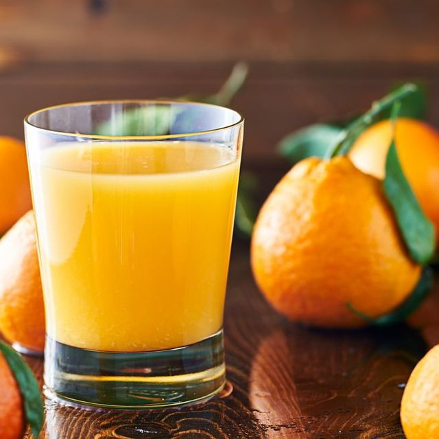 glass of orange juice with oranges