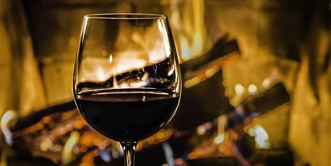 A glass of red wine standing in front of the fireplace. Close up