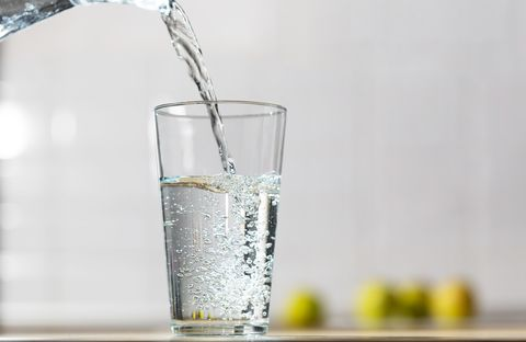 glass of water is poured from the jug into a glass in a kitchen table