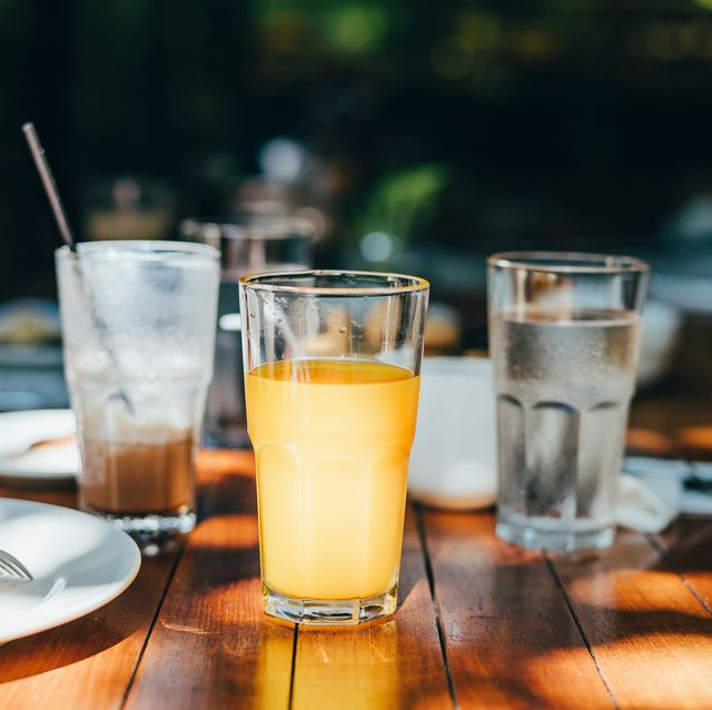a glass of water, orange juice and coffee served on table in an outdoor restaurant against beautiful sunlight