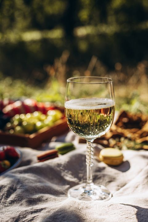 glass with white wine on a picnic background