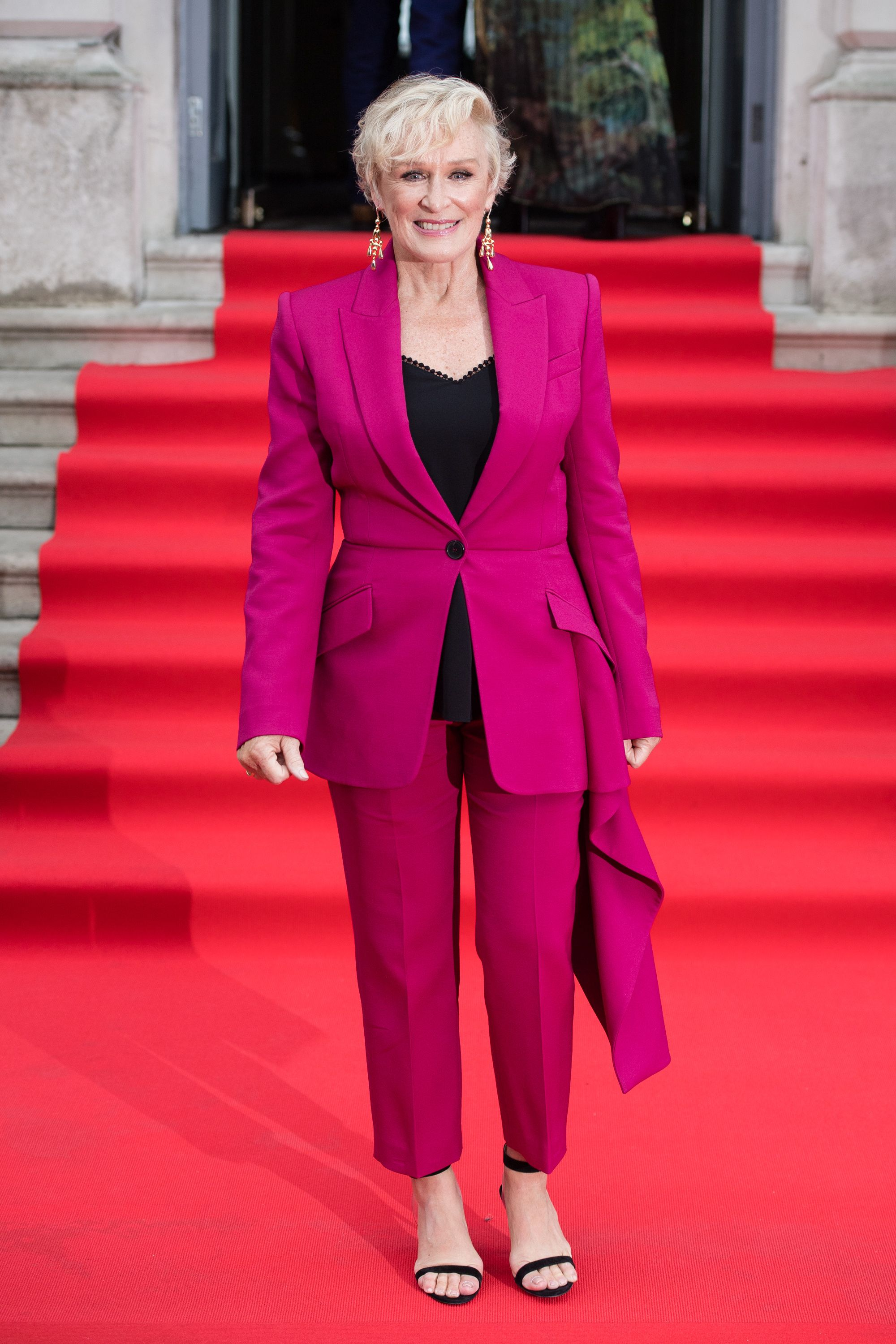 To the UK premiere of The Wife at Somerset House, Close wore a striking magenta suit by Alexander McQueen. The actress highlighted the suit's ruffle detail by wearing a simple black camisole underneath with black heels and dangling earrings.
