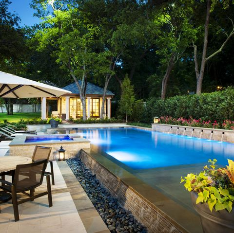 stone surrounded backyard swimming pool