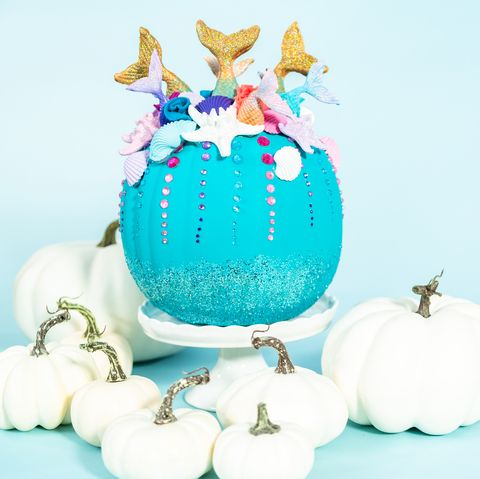 halloween craft pumpkins decorated with mermaid tails, glitter, and sparkly rhinestones on a blue background