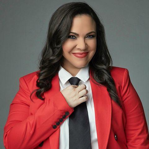 gloria calderón kellett is shown wearing a red blazer, white blouse, black pants and black tie