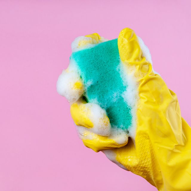 gloved hand holds a foam sponge on a pink background copy space