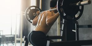 Midsection Of Man Squatting In Gym