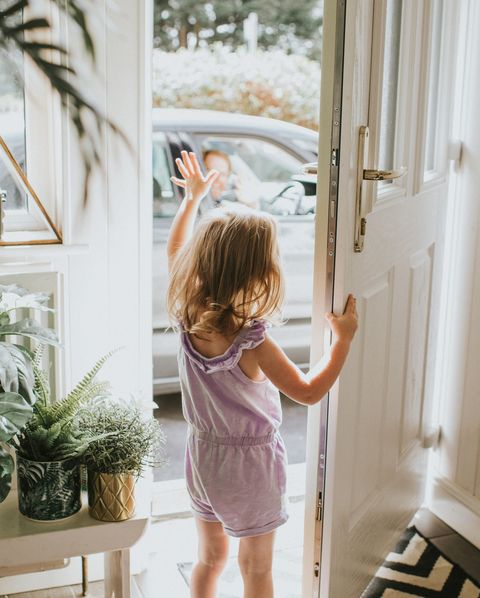 cute little girl waving out the door in a sunny hallway