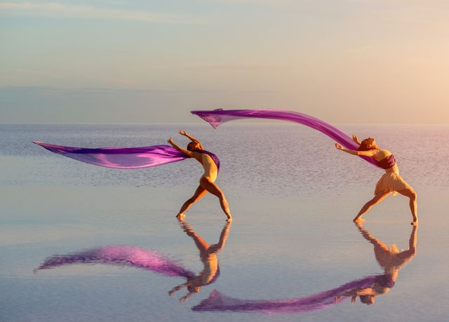 2 dancers on the beach with long purple flowing material