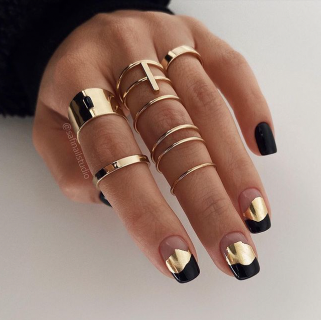 on the left, a hand with black and gold nails and gold rings on a white background, and on the right, a hand with matte black and gold nails on a light brown and white wood background