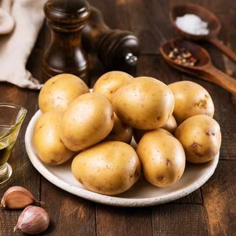 Gold yukon potatoes and cooking ingredients on wooden background