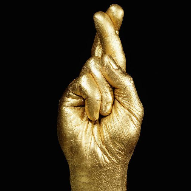 golden hand, fingers crossed