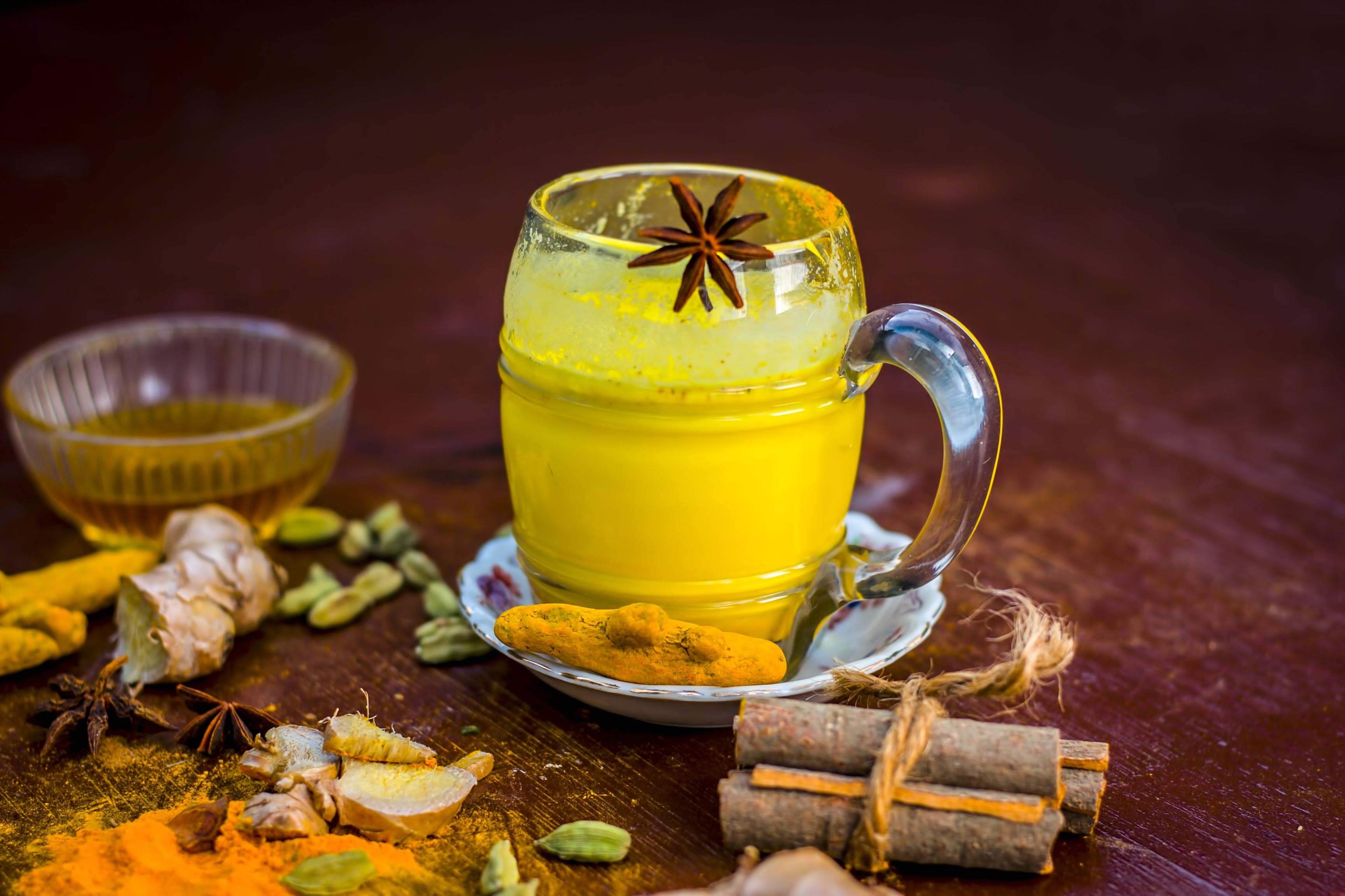 Golden milk with species like green cardamom,turmeric,cinnamon,honey and ginger on wooden surface.