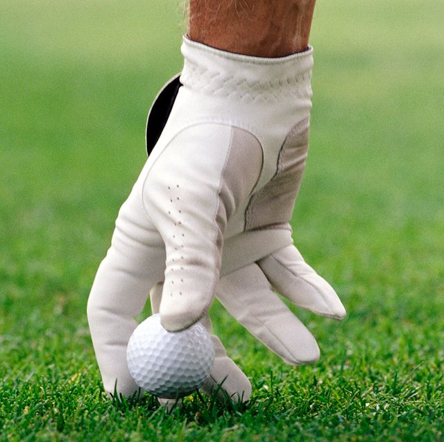 hand in golf glove picking up ball on green
