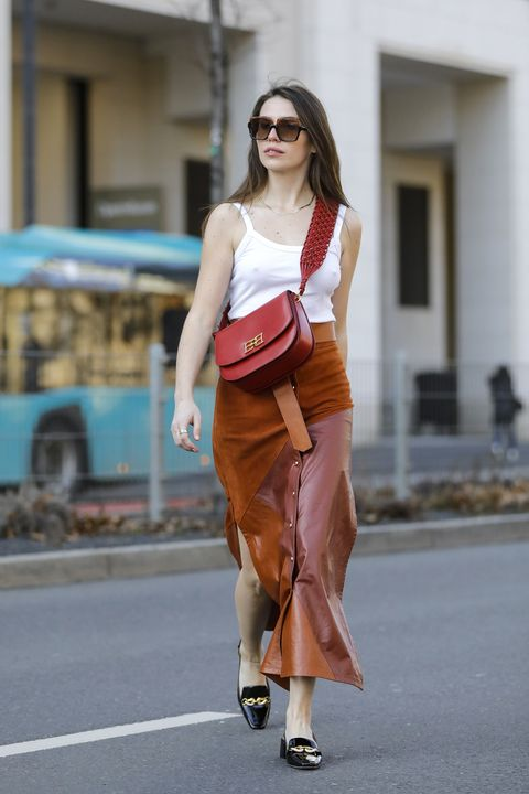 frankfurt am main, germany   march 01 influencer sarah lou falk wearing black shoes by tory burch, a white top by zara, a long cognac colored maxi skirt with gold buttons and high slits by bally, a red bag by bally and sunglasses by gucci during a street style shooting on march 1, 2021 in frankfurt am main, germany photo by streetstyleshootersgetty images