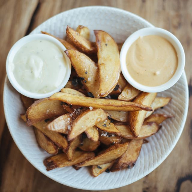 Gourmet potato wedges served with black sea salt & aioli in a white bowl, shot directly above
