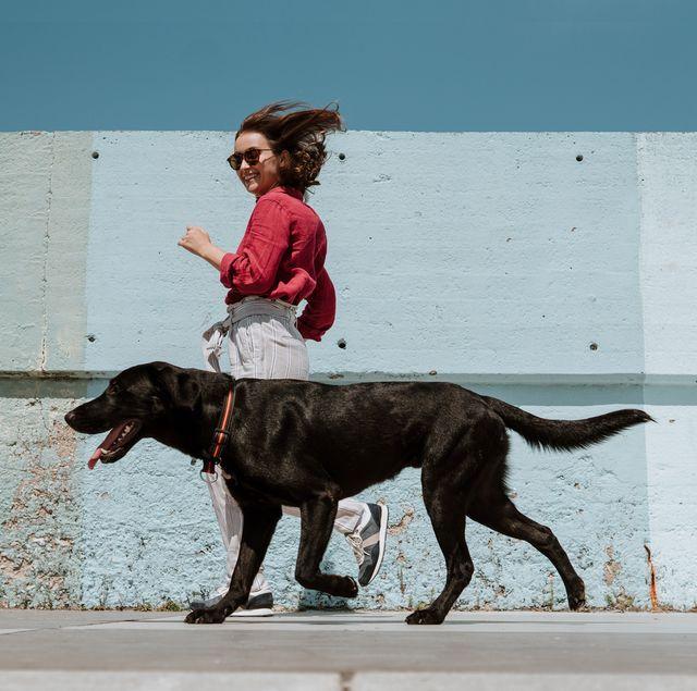 woman running alongside dog